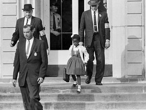 US deputy marshals escort 6-year-old Ruby Bridges from William Frantz Elementary School in New Orleans in November 1960. Source [https://www.flickr.com/photos/usembassythehague/8443765417]